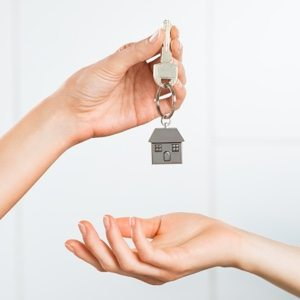 A hand holding a key and a house shaped keychain over another hand