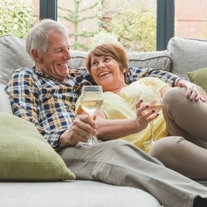 A man and woman sitting on a couch each holding a glass of wine